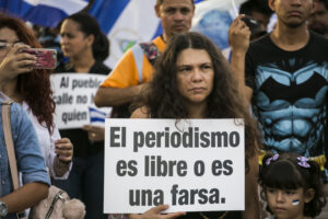 Woman holding sign at tribute to journalist killed in Nicaragua
